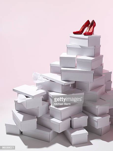 Single pair of red shoes on top of shoe boxes