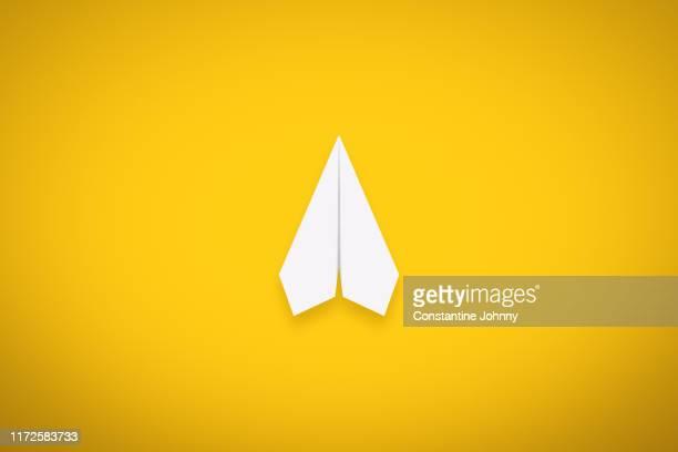a single paper airplane on yellow background - aeroplano di carta foto e immagini stock