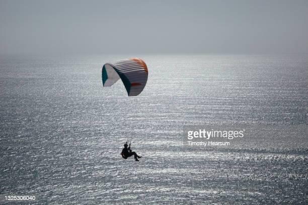 single paraglider over a sparkling ocean - timothy hearsum fotografías e imágenes de stock