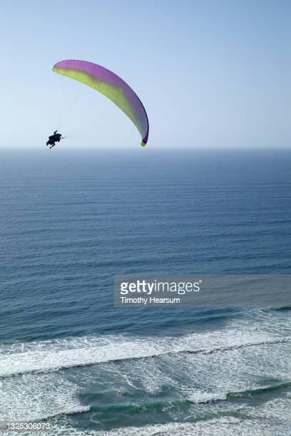 single paraglider over the ocean as waves roll in - timothy hearsum fotografías e imágenes de stock