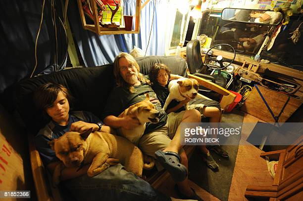 WOOLLARD 'USPOVERTYHOMELESS' Single parent Jess Jessop sits with his sons Thomas 12 and David and their three dogs in the converted bus in which all...