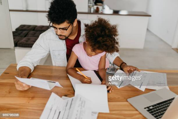 single parent struggling with debt - fun calculator stock photos and pictures