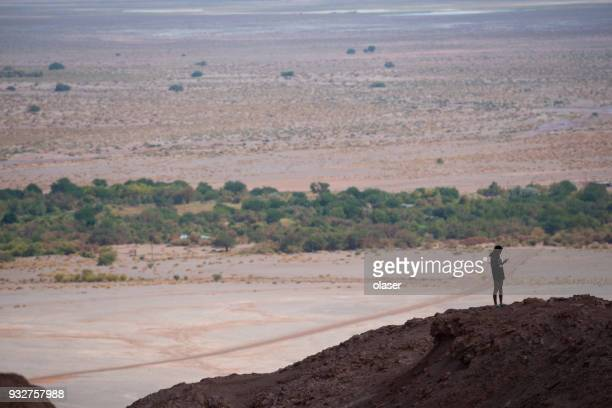 single person on mountaintop. using phone. moon valley in background. - antofagasta region stock photos and pictures