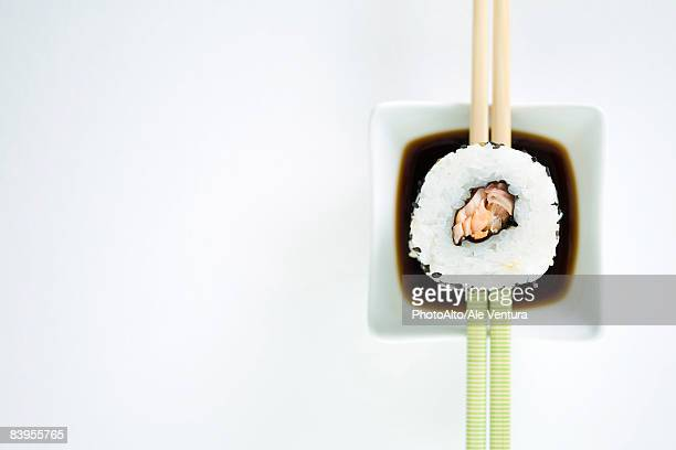 Single piece of maki sushi resting on chopsticks over sauce, overhead view
