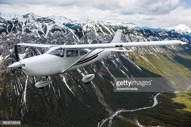 Single prop plane flies above snowy mountains