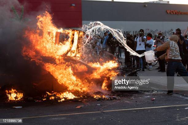 A single protestor tries to help contain a car fire on Thursday May 28 during the third day of protests over the death of George Floyd in Minneapolis...