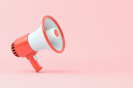 Single red and white electric megaphone with a handle stands on a pink background 1180214258