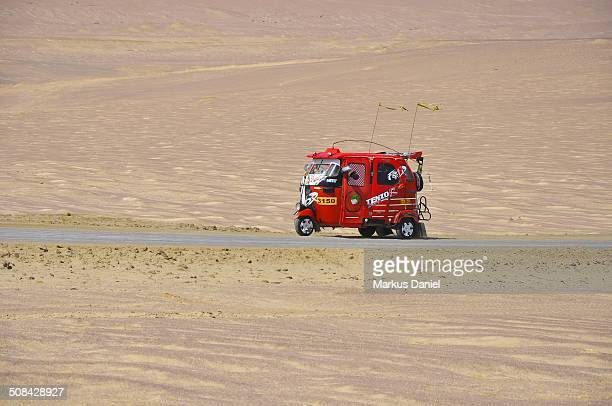 CONTENT] A single red auto rickshaw taxi driving along a salt road in the desert of Paracas National Reserve on a sunny day near Paracas Ica Region...