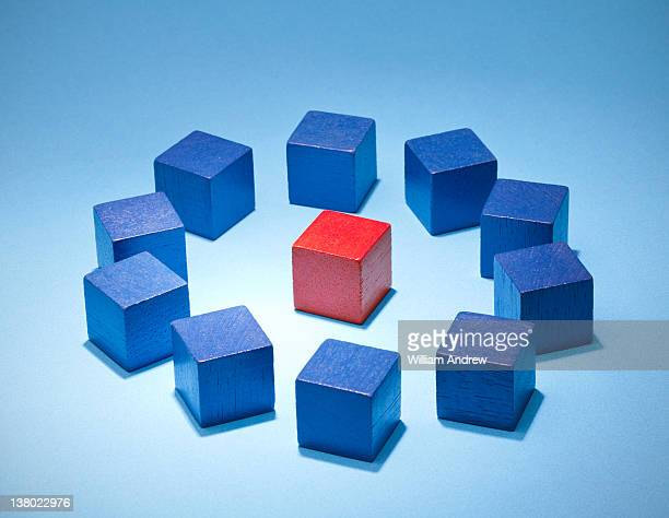 Single red cube surrounded by blue cubes