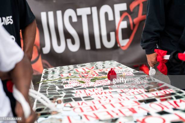 Single rose is laid atop of a coffin art piece by Visual Black Justice during the inaugural remembrance rally and march hosted by the George Floyd...