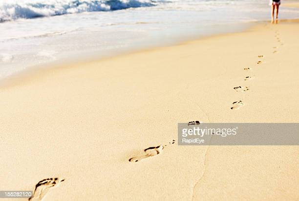 Single row of footprints on beach leading to distant person