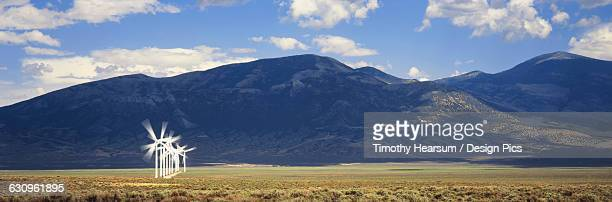 single row of wind generators with mountains beyond, near milford - timothy hearsum stock photos and pictures