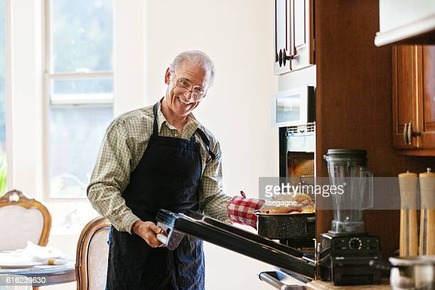 Single senior man cooking turkey