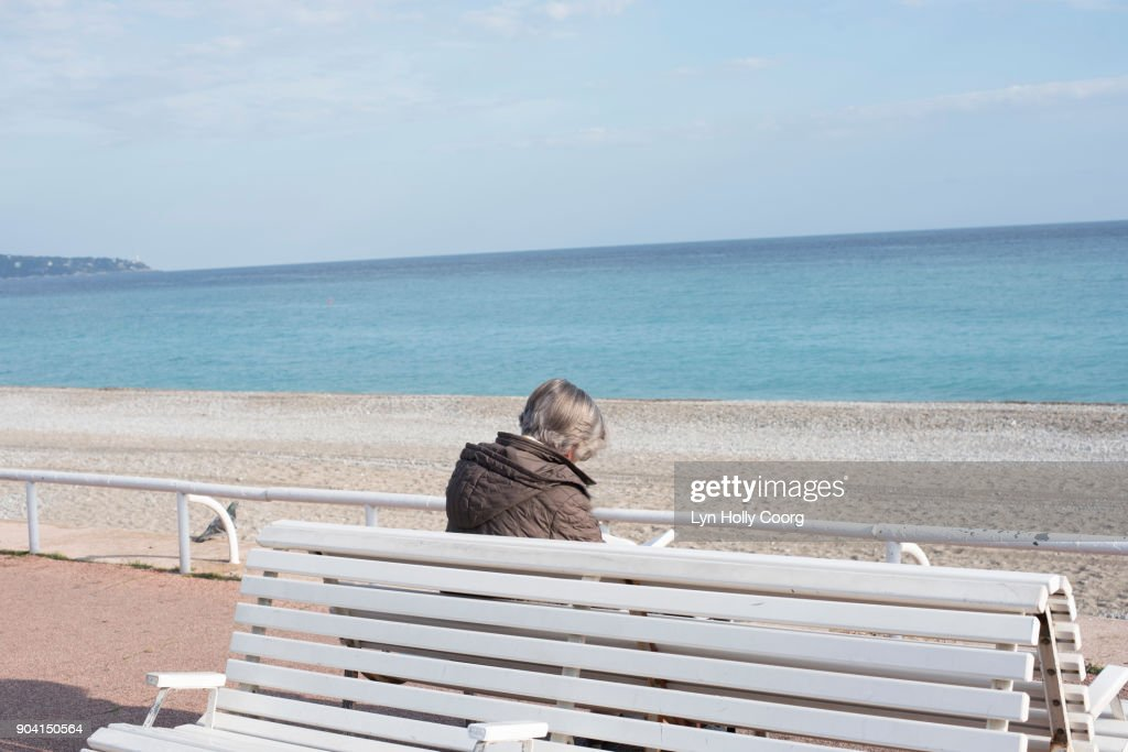 Single senior woman on bench by the sea : Stock Photo