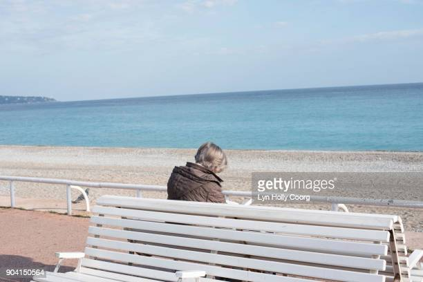 single senior woman on bench by the sea - lyn holly coorg stock-fotos und bilder