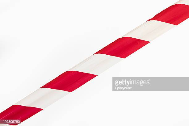 A single strip of red and white striped cordon tape