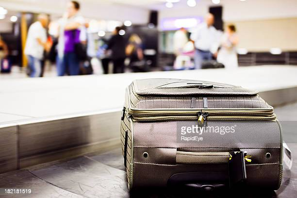 Single suitcase on luggage carousel in  airport arrivals hall.