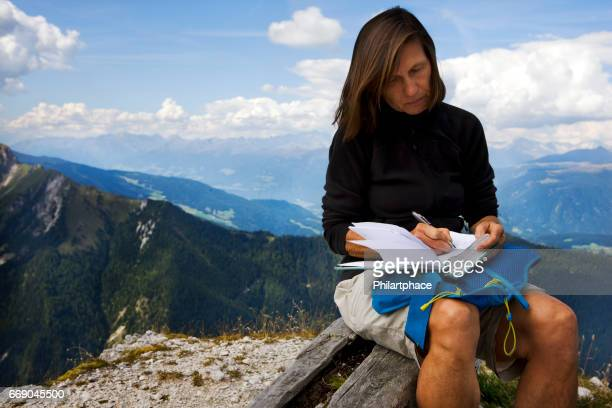 single trekking mature woman sitting on mountain top writing book