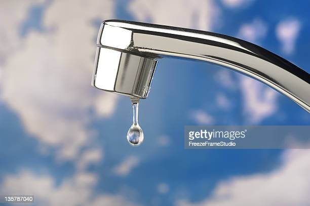 single water drop from stainless faucet; clouded blue sky background - slow motion stock pictures, royalty-free photos & images