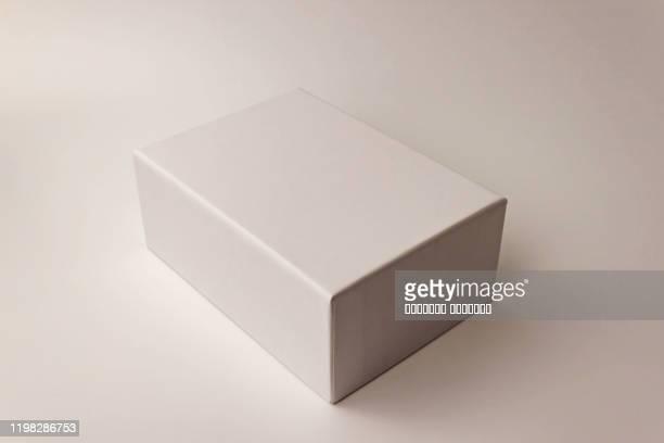 single white paper box on light background. packing, transportation, moving, present concept - caixa imagens e fotografias de stock