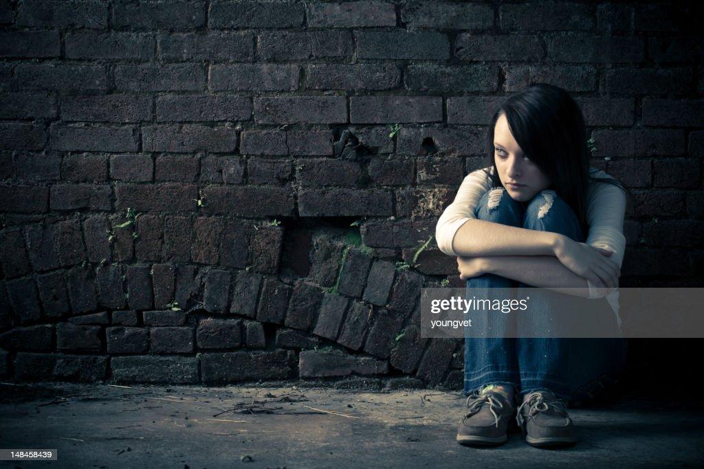 Single woman holding her knees on the street : Bildbanksbilder
