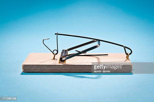 Single wooden mousetrap isolated on blue, side view, studio shot
