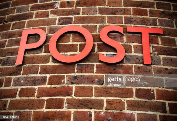 Single word POST on curved brick wall