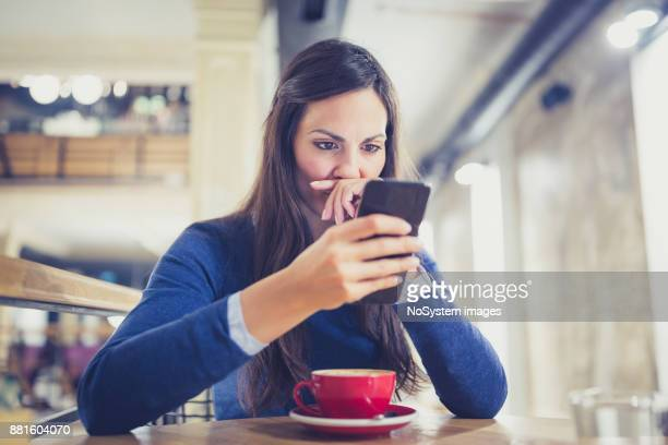 Single. Worried young woman using smart phone in cafe