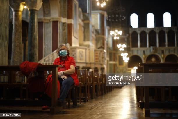 Single worshipper wearing a surgical mask sits on a pew in Westminster Cathedral in central London on March 17, 2020. - Britain on Tuesday ramped up...