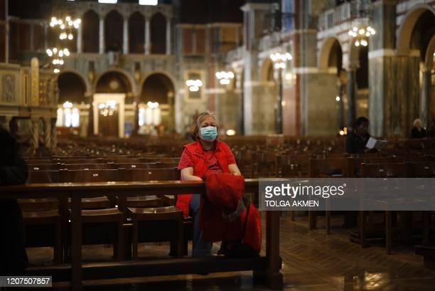 A single worshipper wearing a surgical mask sits on a pew in Westminster Cathedral in central London on March 17 2020 Britain on Tuesday ramped up...