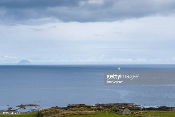 Single yacht in Scottish landscape with in the background Ailsa Craig island in the Firth of Clyde south of the Isle of Arran Scotlandn