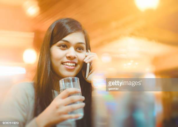 Single young woman at restaurant talking on smart phone.