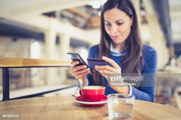 Einzelne. Junge Frauen online-shopping in Café, Zahlung mit Karte