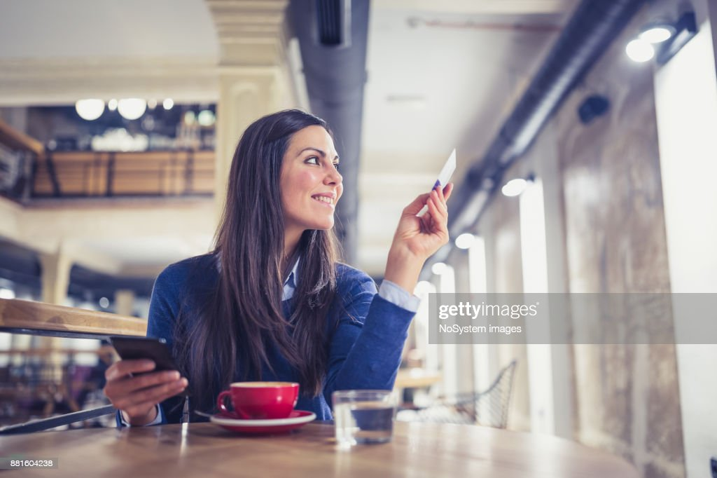 Single. Young women shopping online in cafe, paying with card : Stock Photo