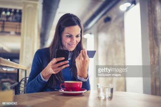 Single. Young women shopping online in cafe, paying with card
