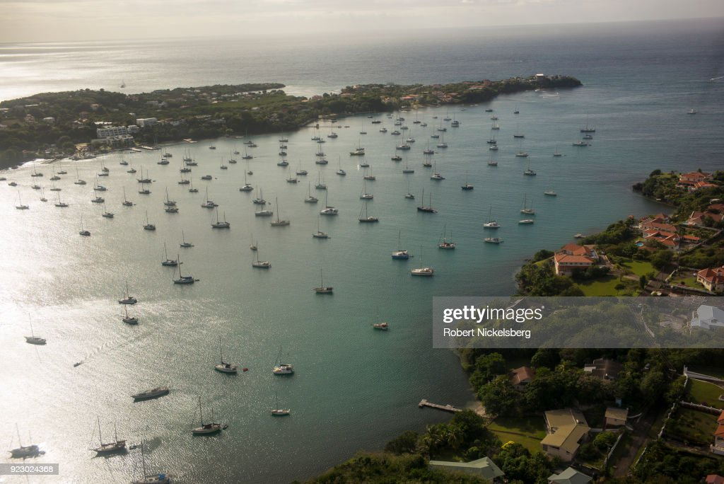 A single-engine plane flown by SVG Air flies over a sailboat filled harbor February 2, 2018 west of St. George's, Grenada.