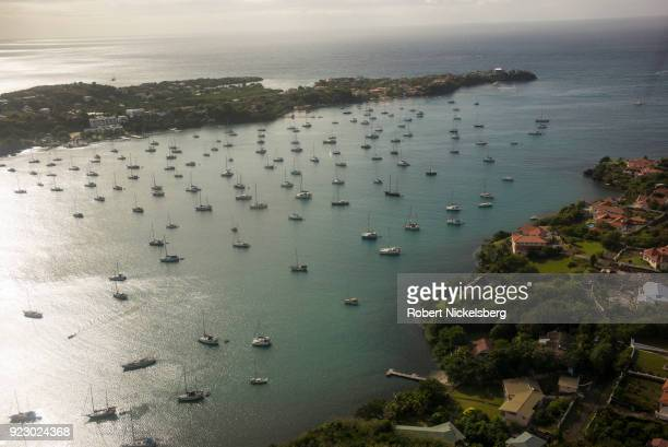 A singleengine plane flown by SVG Air flies over a sailboat filled harbor February 2 2018 west of St George's Grenada