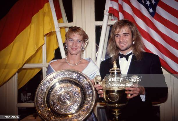 Singles champions Steffi Graf of Germany and Andre Agassi of the USA pose with their trophies at the Wimbledon Champions' Dinner after the Wimbledon...