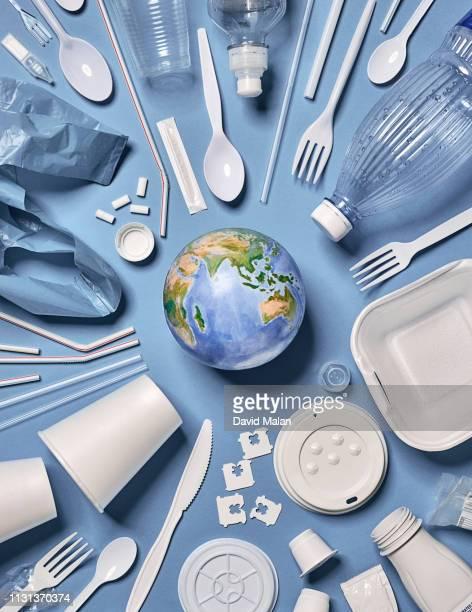 single-use plastic objects arranged around the earth. - 使い捨て製品 ストックフォトと画像