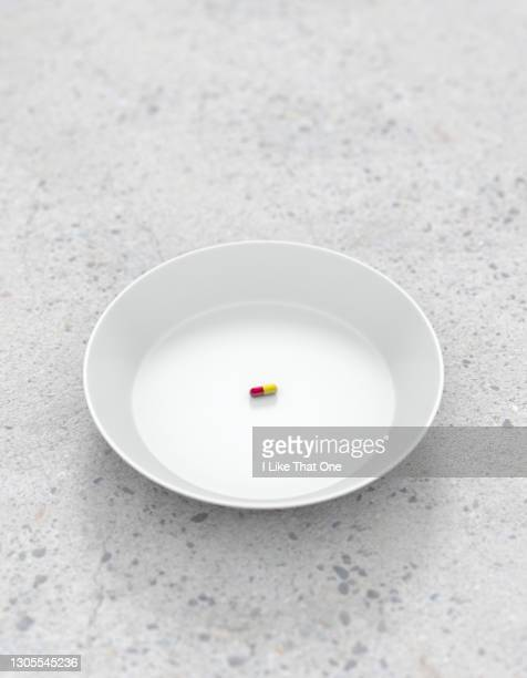 a singular medication pill on a plate - atomic imagery stock pictures, royalty-free photos & images