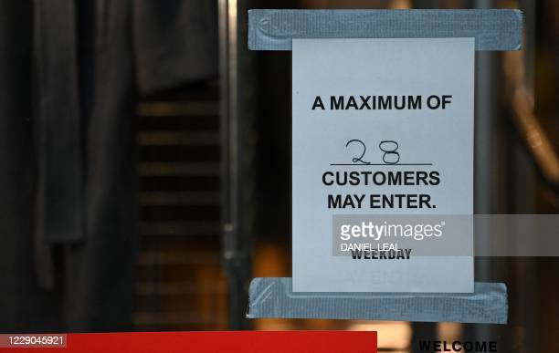 Sinh on the door of a shop alerts customer to the store's maximum capacity, due to COVID-19, on Regent Street in London on October 13 following the...