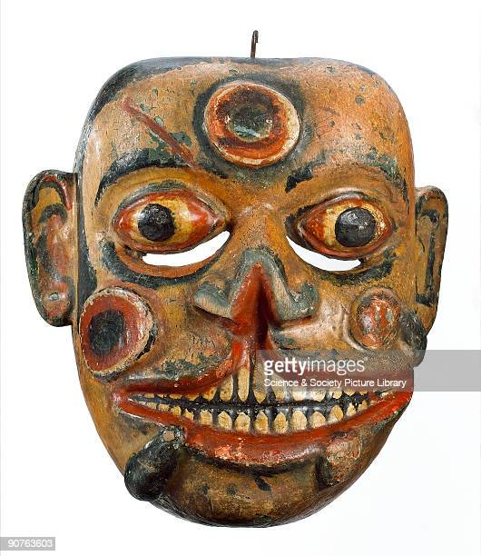 Sinhalese carved and polychrome painted wooden face mask representing Hevaya the soldier from the kolam play his face covered with sores and leeches