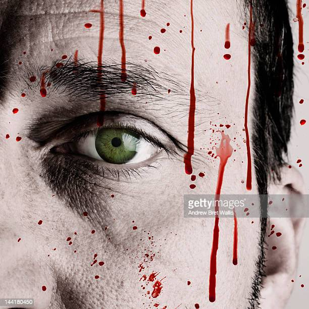sinister man's face behind blood stained glass - murder stock pictures, royalty-free photos & images