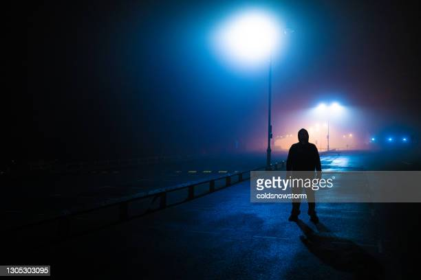 sinister silhouette man lurking in deserted parking lot - murderer stock pictures, royalty-free photos & images