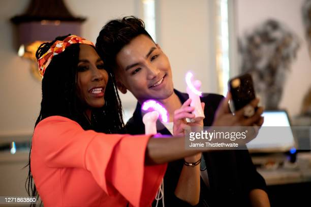 """Sinitta and Vincent Wong take a selfie during the """"Henpire"""" podcast launch event at Langham Hotel on September 10, 2020 in London, England."""