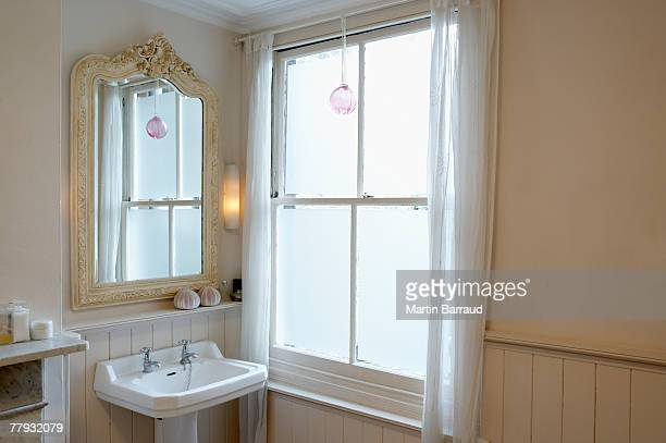 Sink and mirror beside window