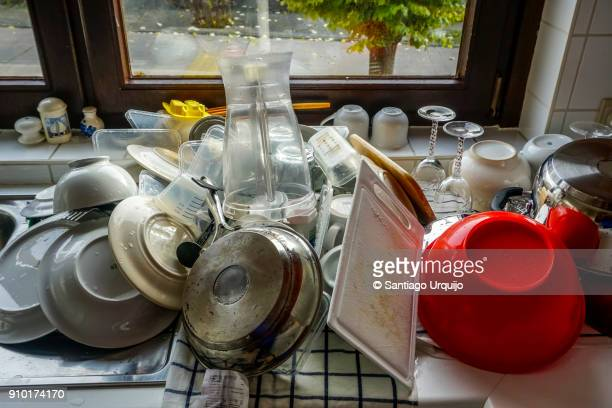 Sink full of washed plates and cutlery