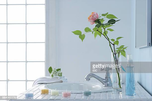 Sink in bathroom with rose in vase and bars of soap