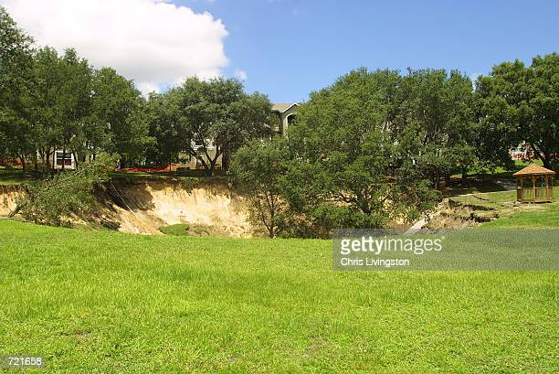 A sinkhole measuring 150 feet wide and about 60 feet deep is shown June 12 2002 a day after it opened near the Woodhill Apartments in Orlando Florida...