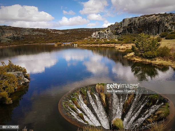 sinkhole on lake by serra da estrela mountain range - sinkhole stock photos and pictures